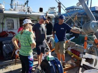 Eric is giving a boat tour and explanation about the different data acquisition​ systems to Steve, Jason, ​and Emily, the chase boat team from UH Hilo marine operation​s.
