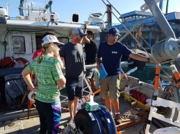 Eric is giving a boat tour and explanation about the different data acquisition systems to Steve, Jason, and Emily, the chase boat team from UH Hilo marine operations.