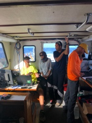 Jason, Khaira, and Eric are discussing water column Multi-beam data, whereas Patrick is operating the G-882 magnetometer system.
